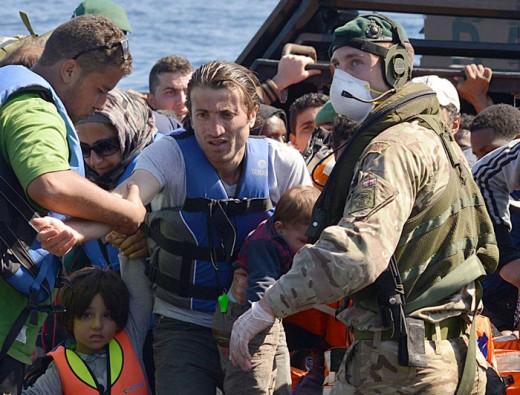Flyktingar får hjälp att kliva ombord på HMS Bulwark i Medelhavet, strax norr om Libyen. Foto: Royal Navy Media Archive (CC-licens)